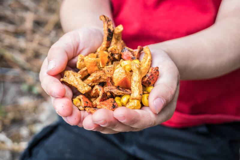 Child holding freeze dried corn and roasted red bell peppers