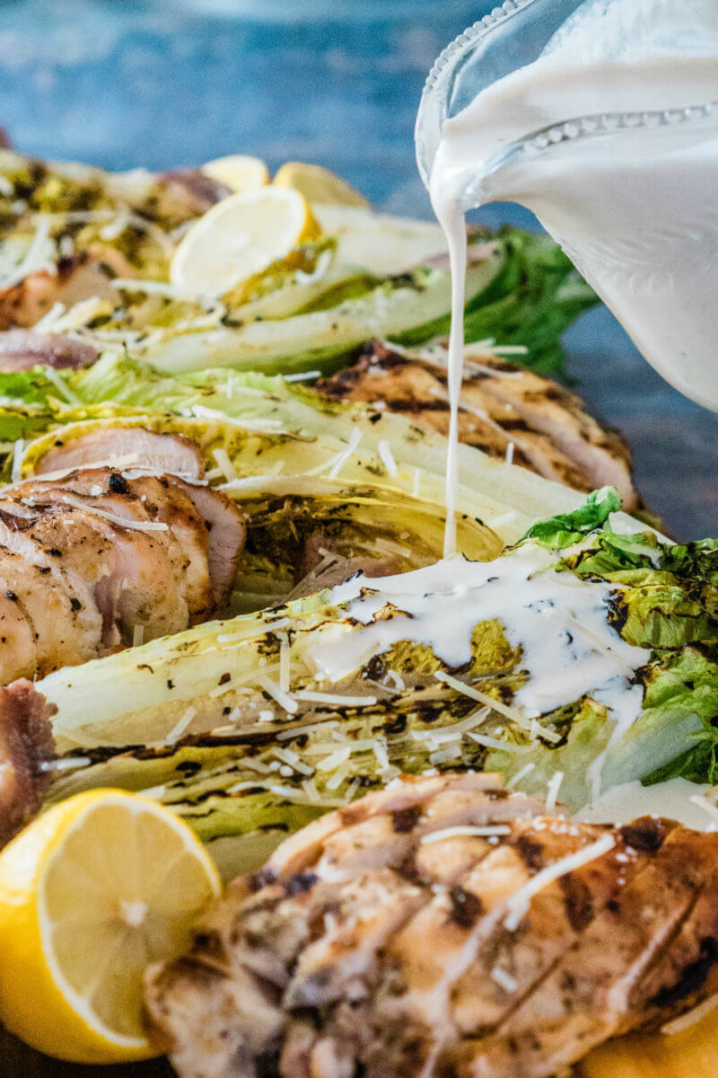 Caesar dressing poured onto grilled romaine hearts and chicken