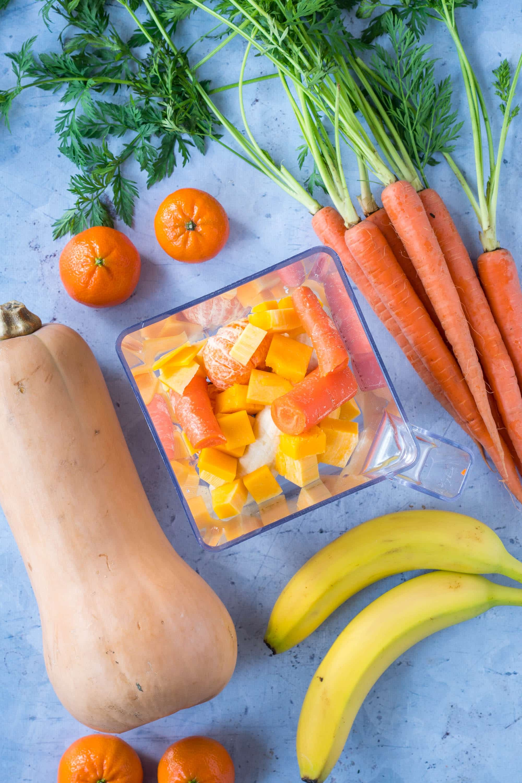 Tangerines, carrots, butternut squash, bananas in a blender