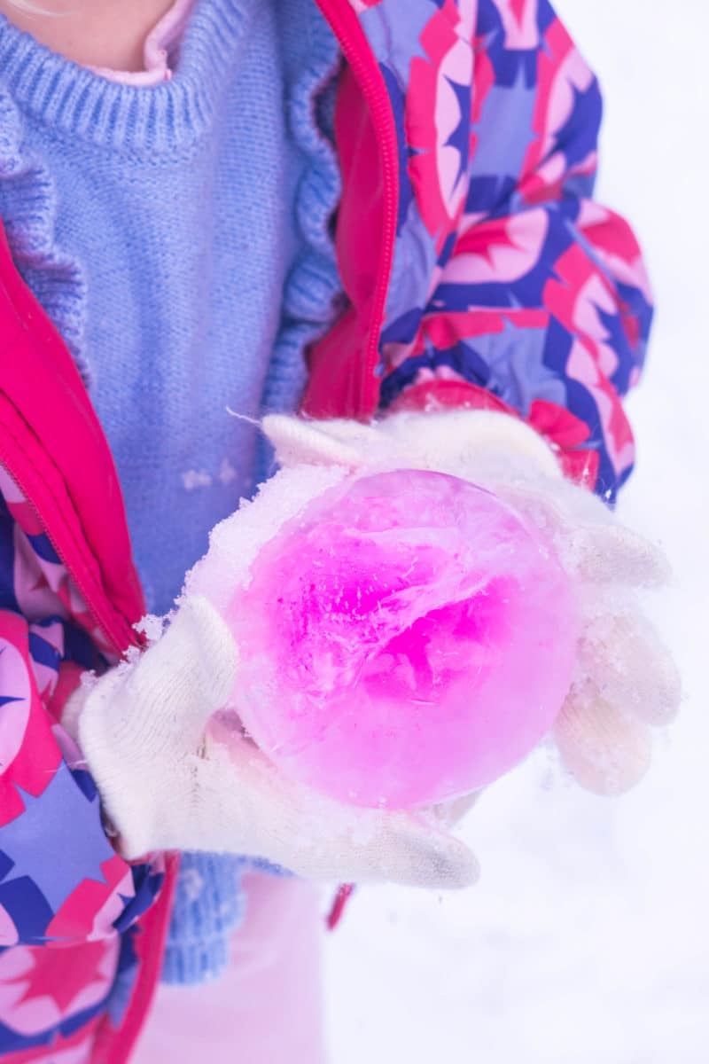 Holding Pink Ice Ball in Snow