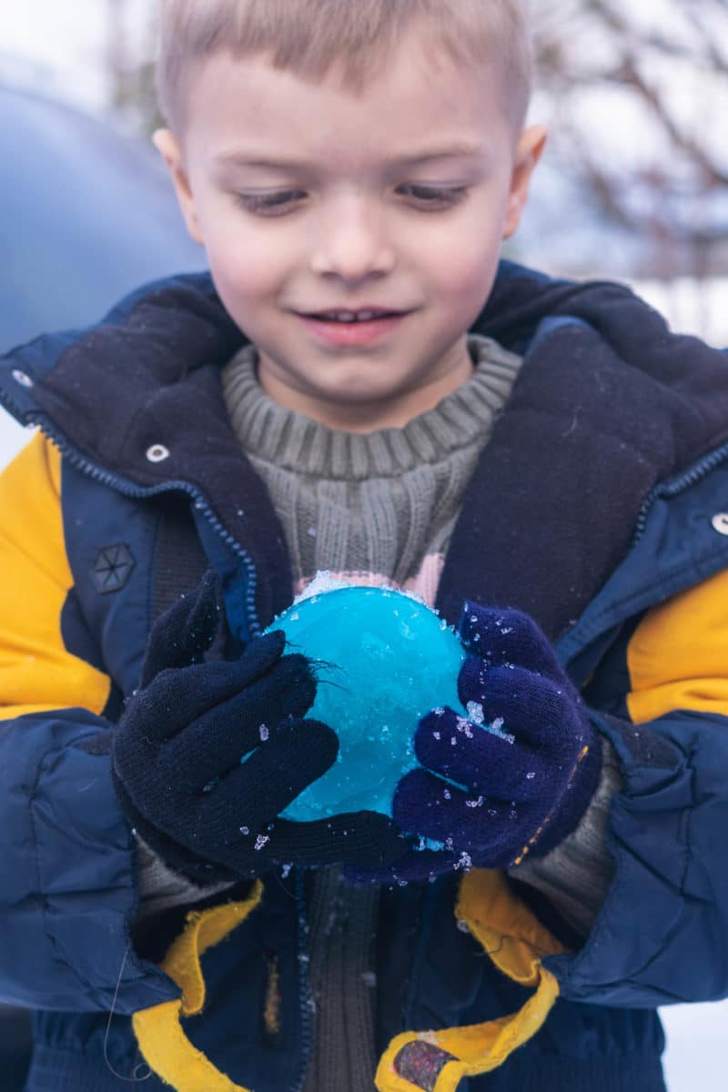Boy holding blue ice balloon ball