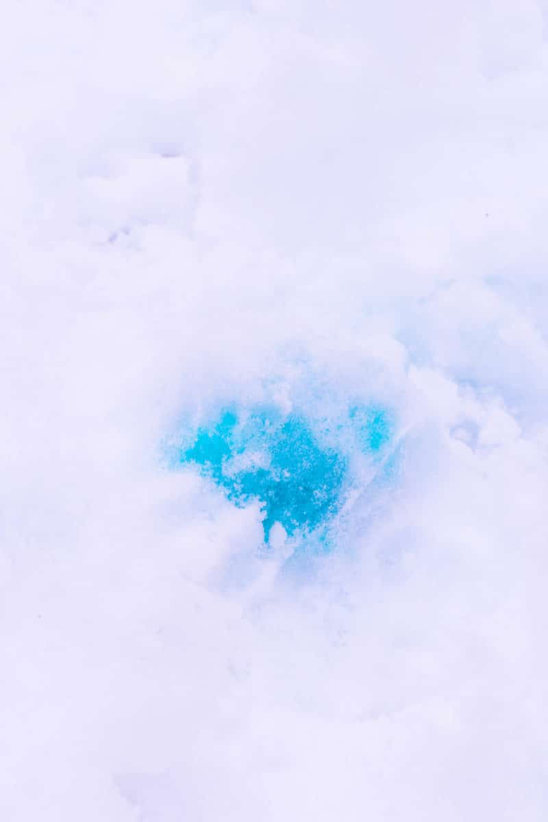 Blue ice balloons buried in snow