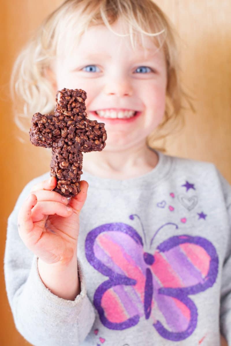 Child holding cross shaped chocolate Rice Krispie Treat