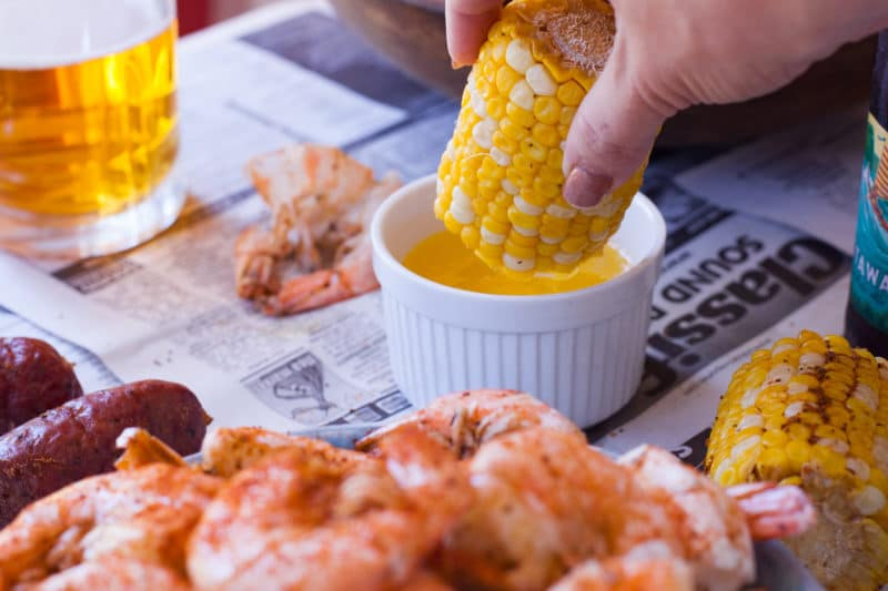 Dipping Corn into Melted Butter at a Shrimp Boil Party
