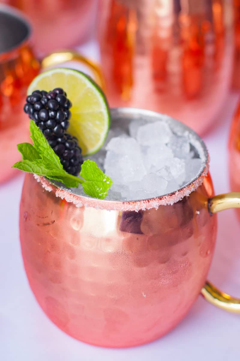 Copper mug with sugar rim, blackberry lime and mint garnishes, and ice