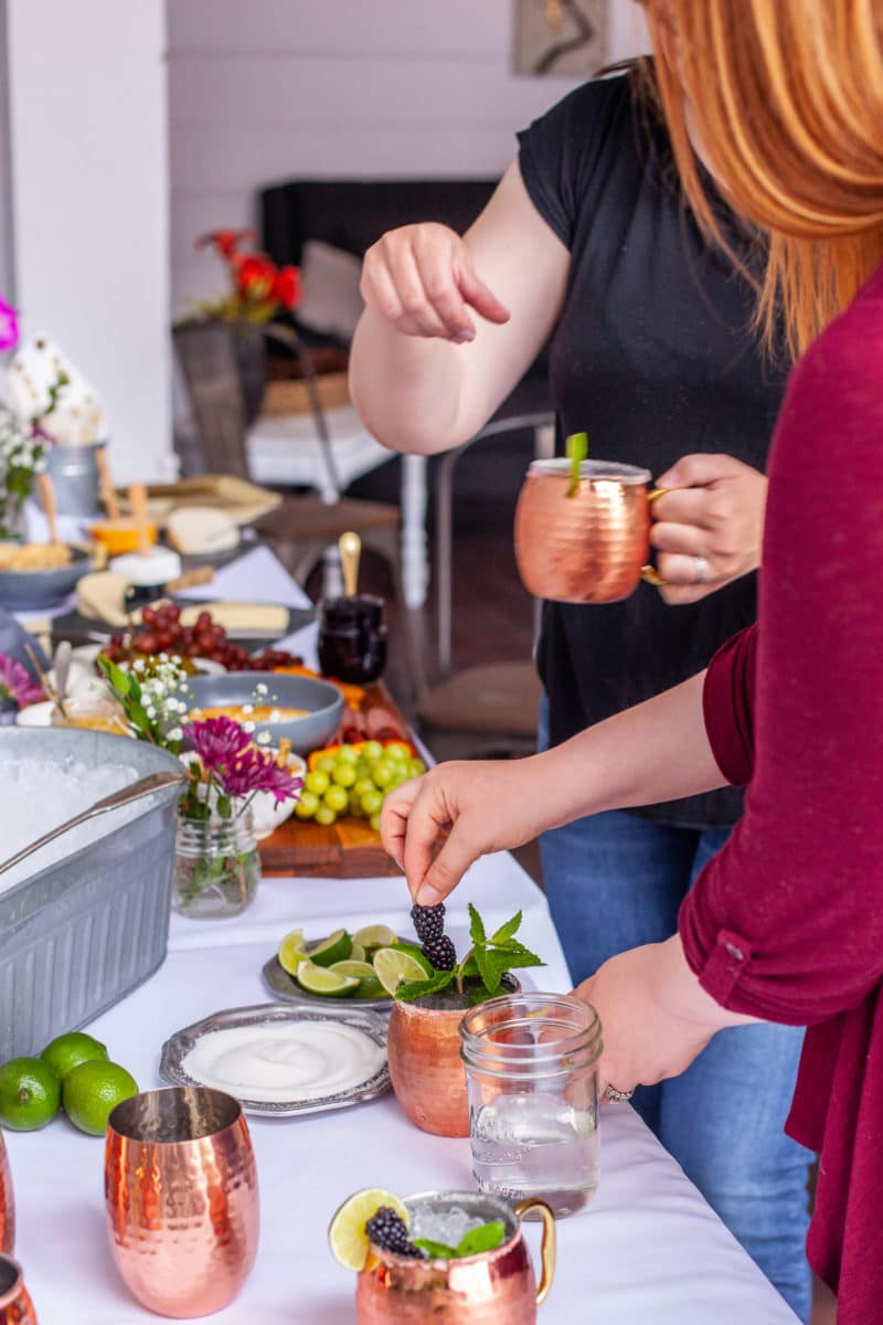 Guests making Blackberry Moscow Mules at a cocktail bar