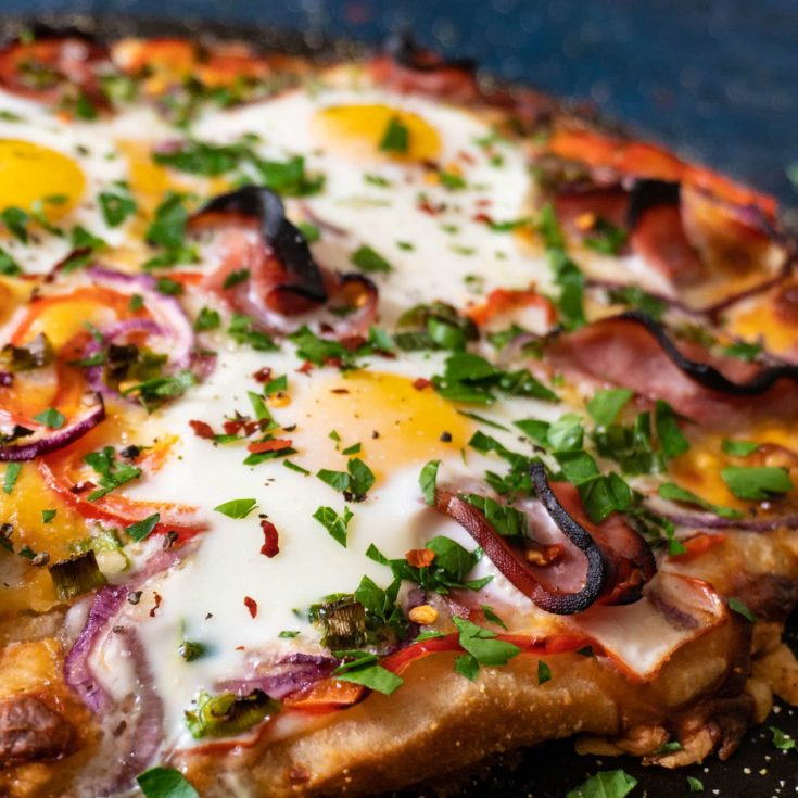 Breakfast pizza topped with crispy ham, sunny side up eggs, red bell pepper, red onion, green onion, parsley, and red pepper flakes