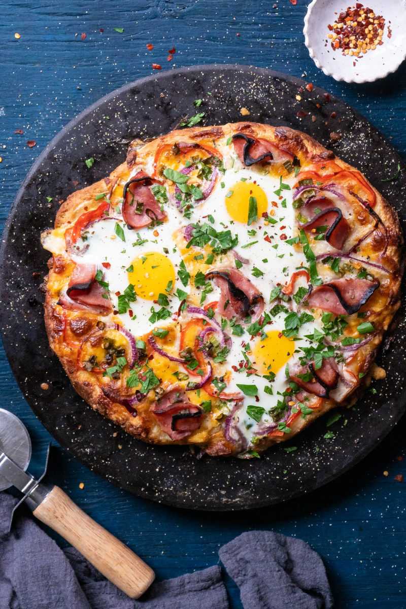 Ham Egg and Cheese breakfast pizza cooked on a pizza stone