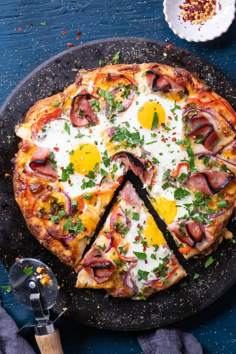 Ham Egg and Cheese breakfast pizza with a slice cut lies cooked on a pizza stone