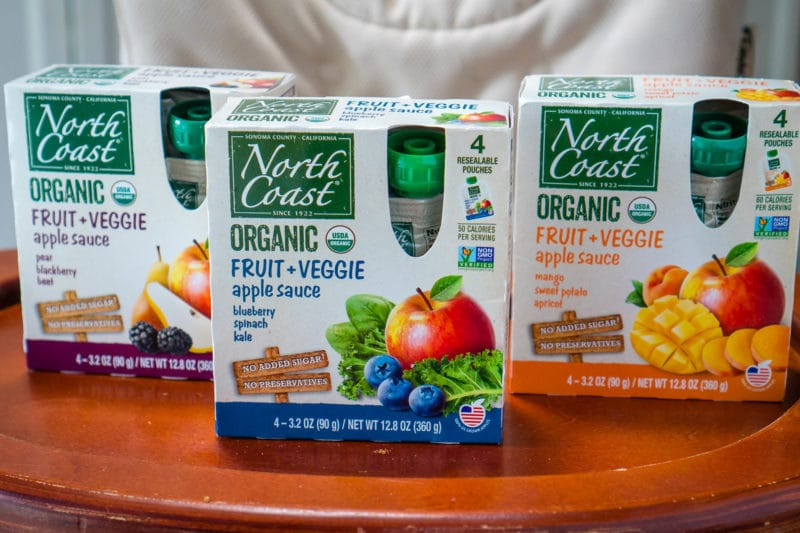 Boxes of North Coast Organic Fruit + Veggie Pouches for Kids on a high chair tray