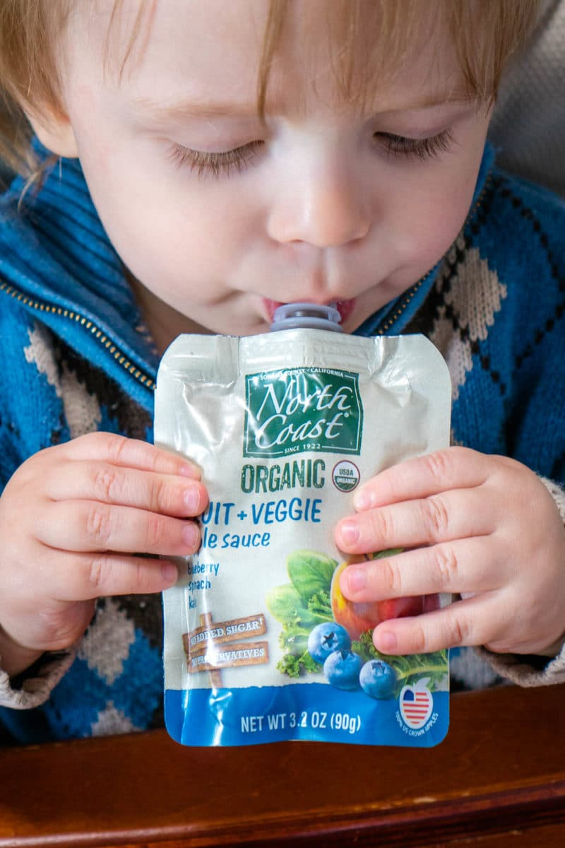 Toddler eating North Coast Organic Fruit + Veggie Pouch