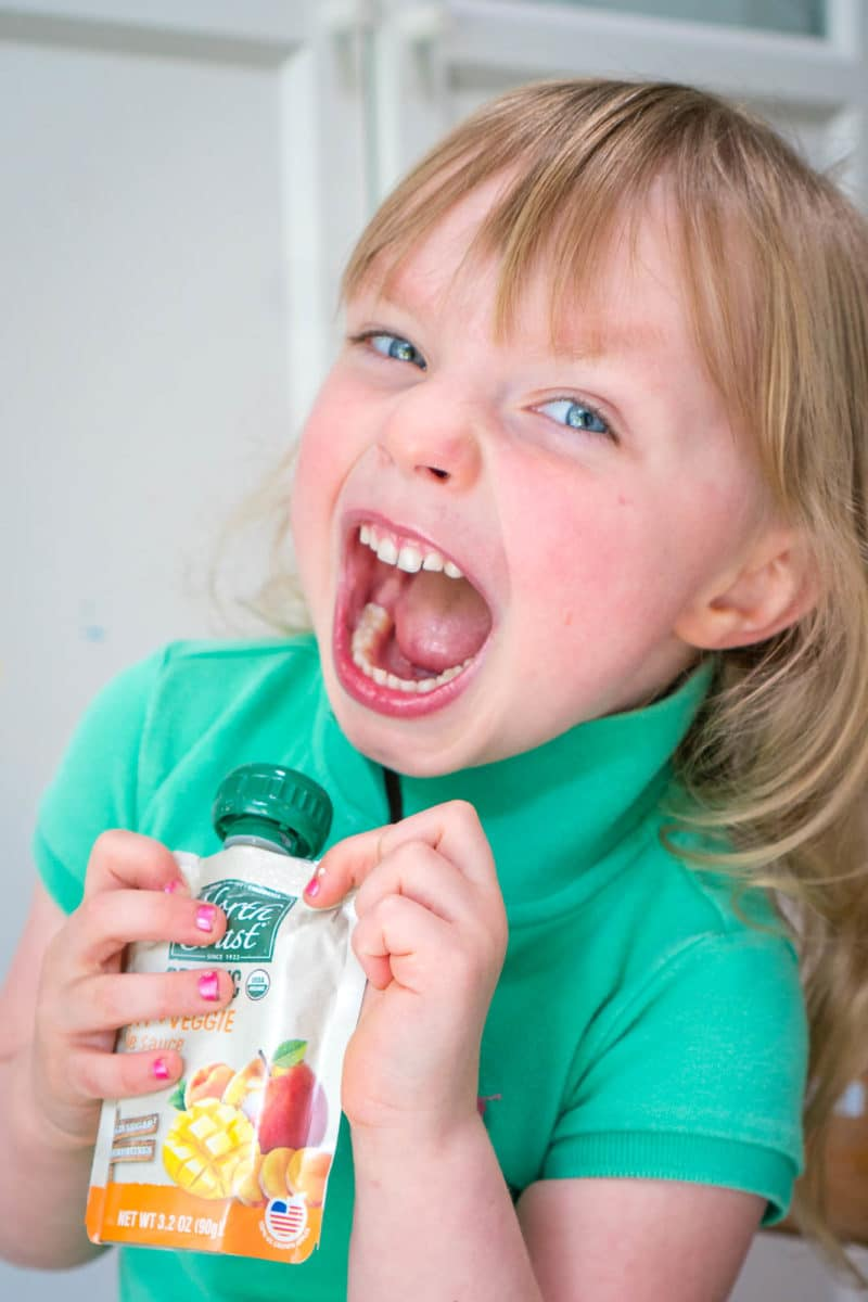 Excited girl holding North Coast Organic Fruit + Veggie Pouch