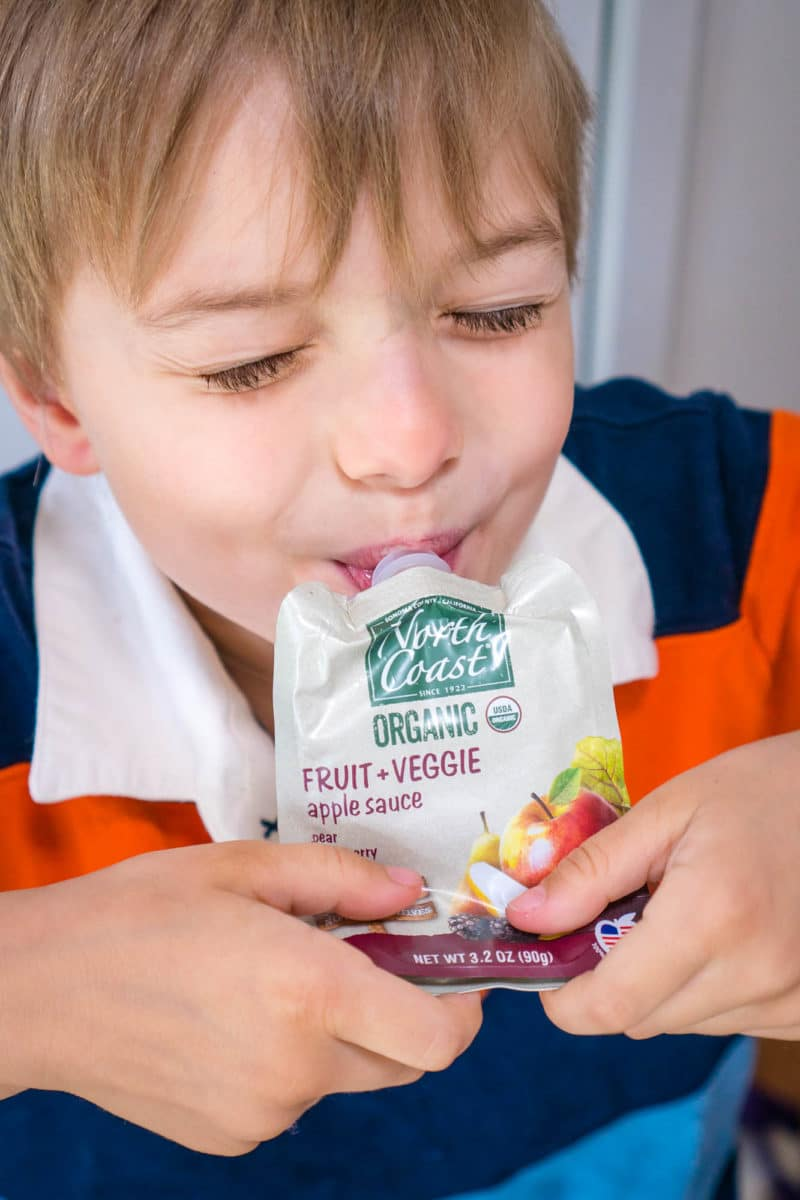 Boy eating North Coast Organic Fruit + Veggie Pouch with apple sauce, pear, blackberry, and beet