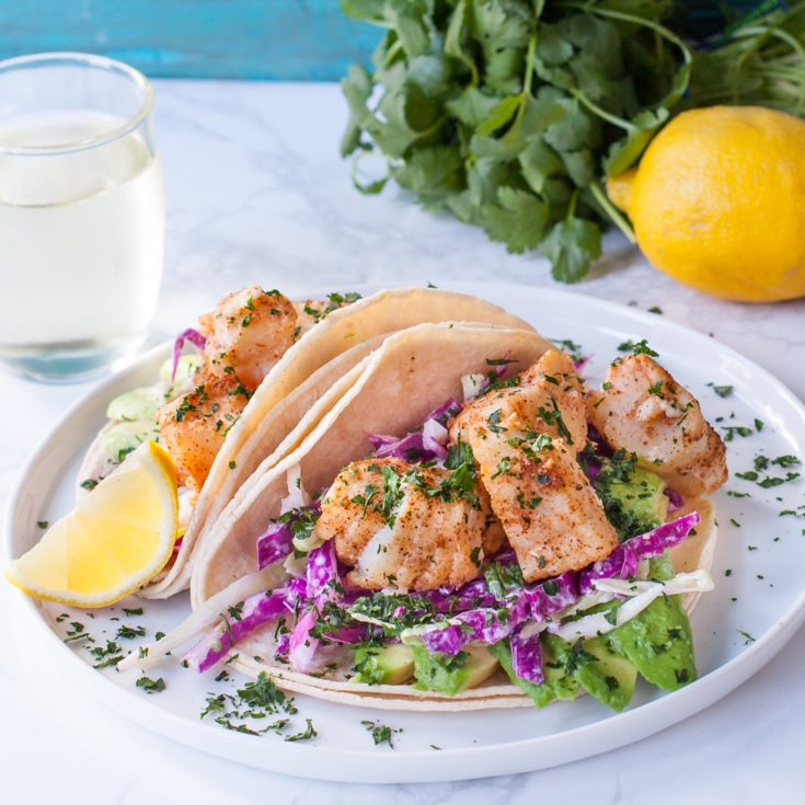 Plate of fish tacos with slaw and avocado