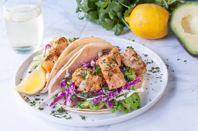 Fish tacos on a plate with red and green slaw and lemon wedge