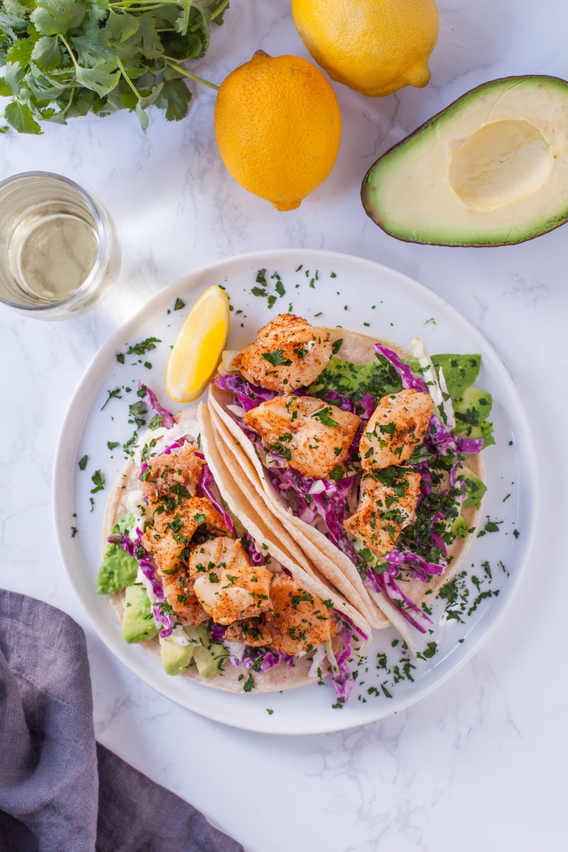 Overhead photo of 2 fish tacos on a plate with avocado, lemons, and cilantro on the table
