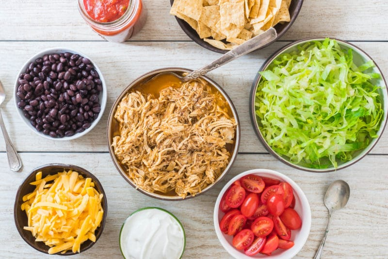 Overhead view of Ingredient bowls for DIY Taco bar including shredded chicken