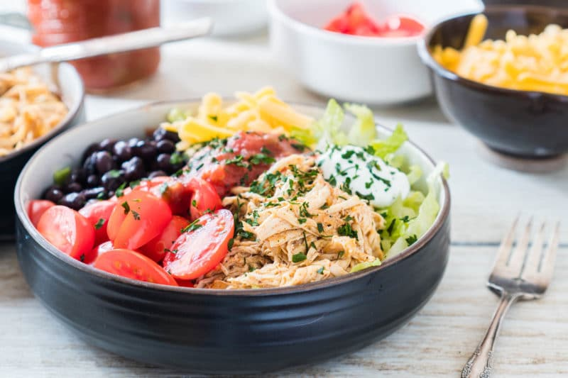 Chicken taco bowl with shredded chicken, lettuce, cheese, black beans, tomatoes, sour cream, and cilantro