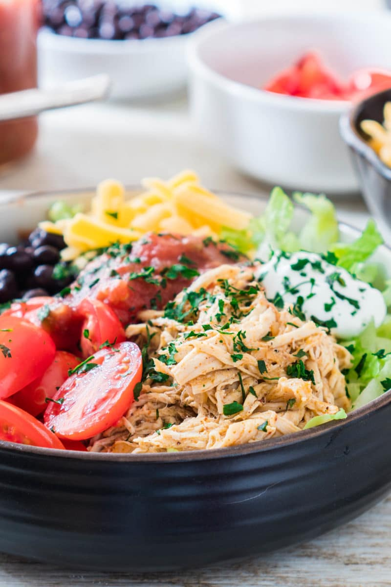 Close up view of chicken taco bowl with shredded chicken, lettuce, cheese, black beans, tomatoes, sour cream, and cilantro