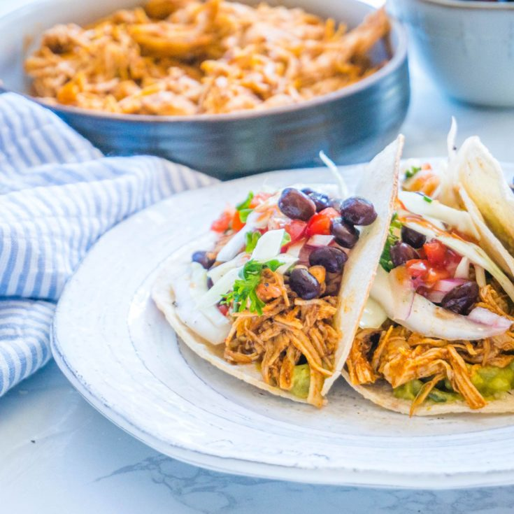 Crockpot Chicken tacos with slaw and black beans with shredded chicken in a bowl in the background
