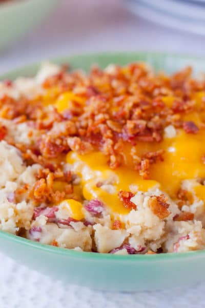 Close up of a bowl of red skin mashed potatoes topped with melted cheddar and chopped bacon
