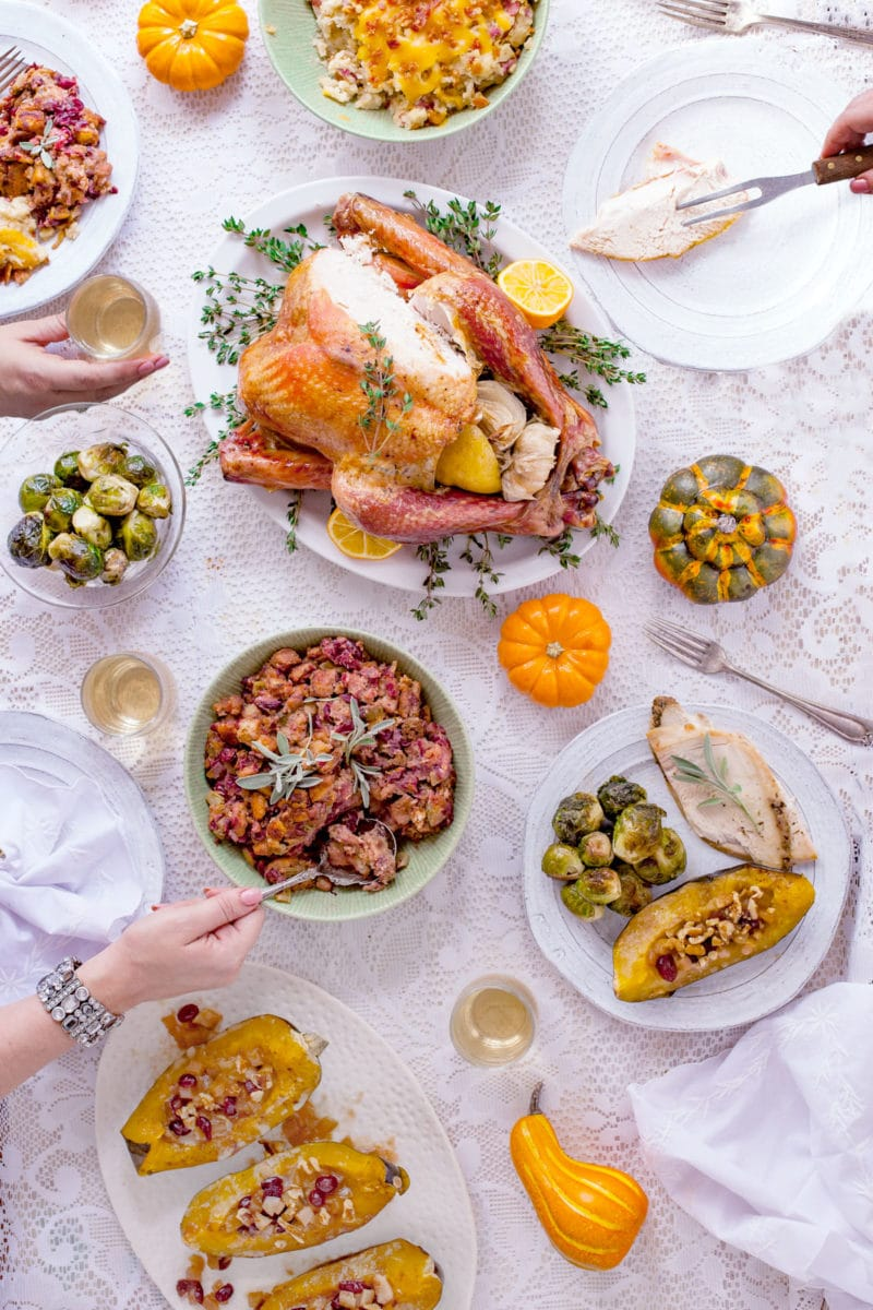 Overhead view of Thanksgiving meal on white tablecloth with hands serving food
