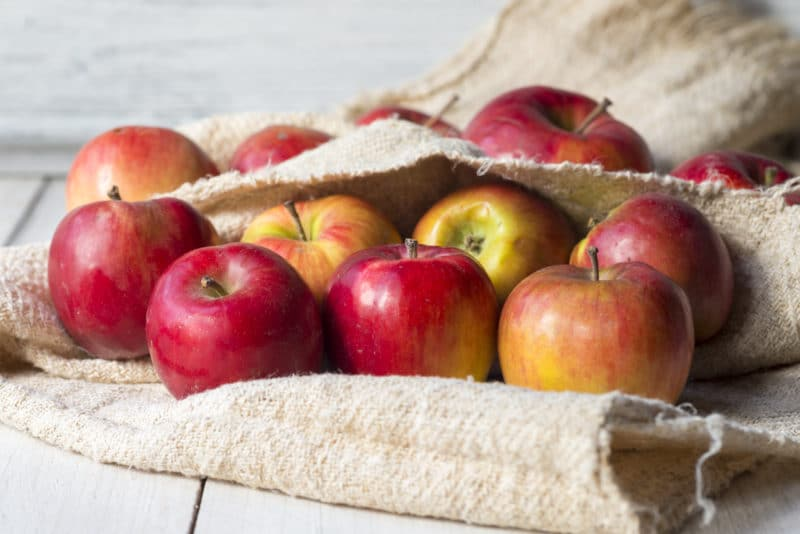 Ripe red apples in burlap cloth on white table
