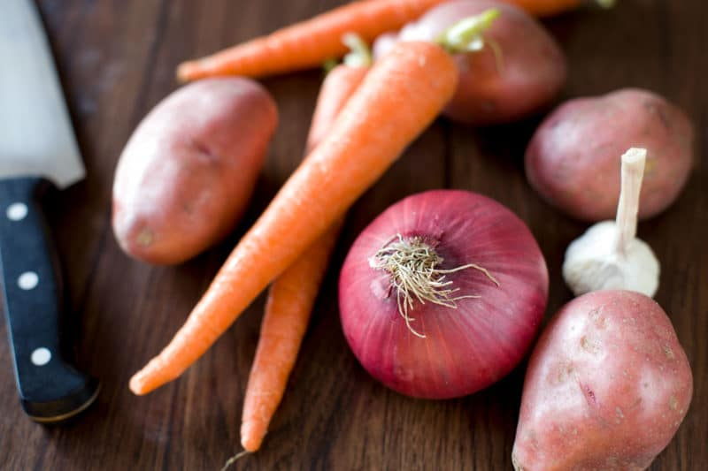 Carrots, Red potaotes, garlic bulb, and red onion on a brown board with a chefs knife