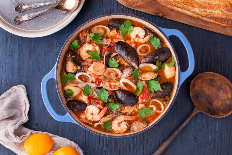 overhead view of blue Dutch oven full of Bouillabaisse stew