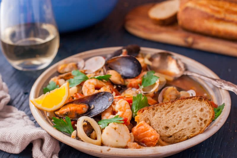 Slice of crusty bread in a bowl of bouillabaisse with assorted seafood, broth, and a lemon wedge