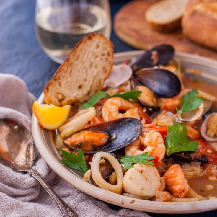 Dinner table set with white wine, bowl of bouillabaisse, and crusty bread