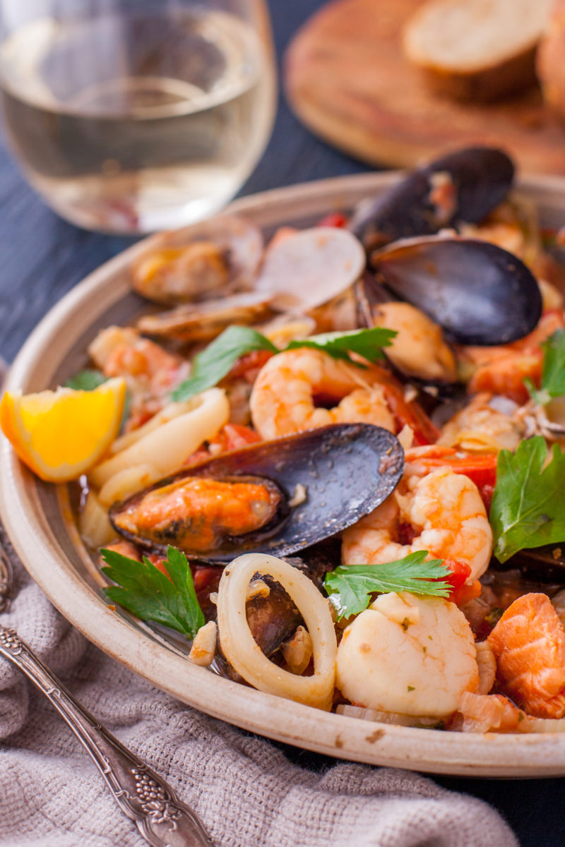 Bouillabaisse with shrimp, scallops, squid, mussels, and clams in a shallow bowl.