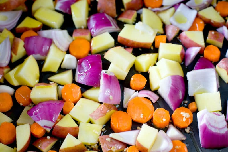 Chopped root vegetables on a black baking sheet