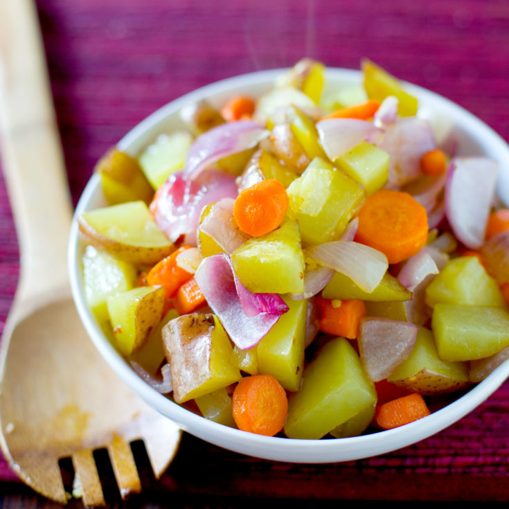 roasted root vegetables in a bowl on maroon placemat with wooden serving spoon