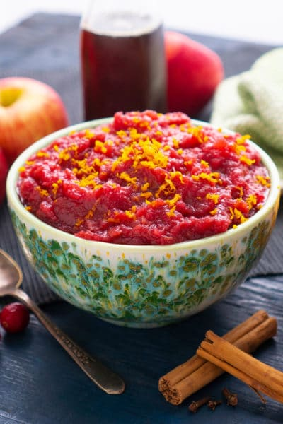 Bowl of cranberry applesauce with bottle of maple syrup behind it