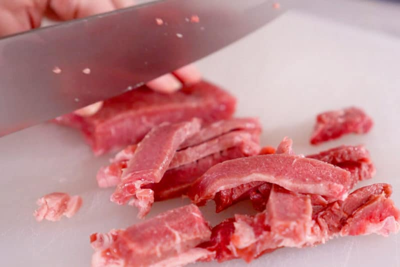 Knife thinly slicing partially frozen sirloin steak