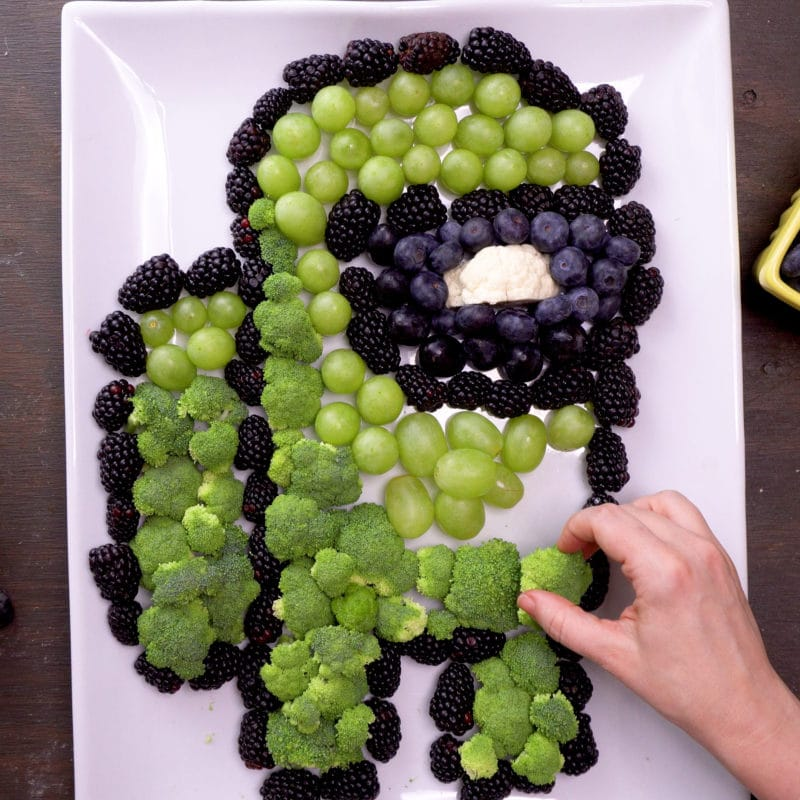 Among Us fruit and veggie tray with visor filled with black grapes, blueberries, and cauliflower