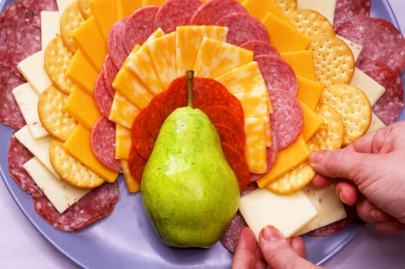 Placing cheese into a turkey shaped cheese board