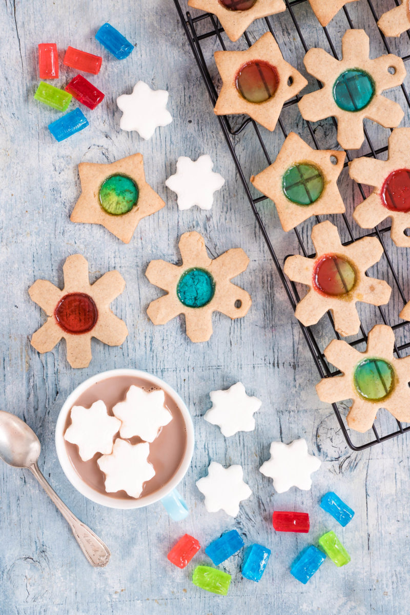 Stained glass cookies on a cooling rack and white wooden table with hot cocoa, snowflake shaped marshmallows, and colorful unwrapped jolly ranchers