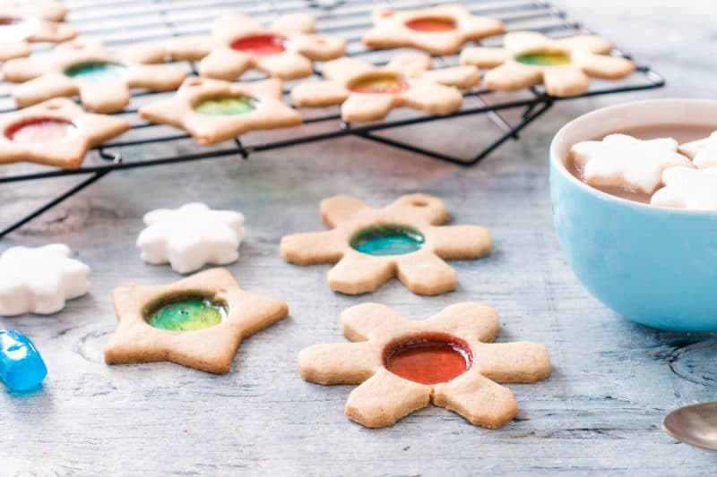 Cookies shaped like stars and snowflakes with see through colorful candy circles in the center