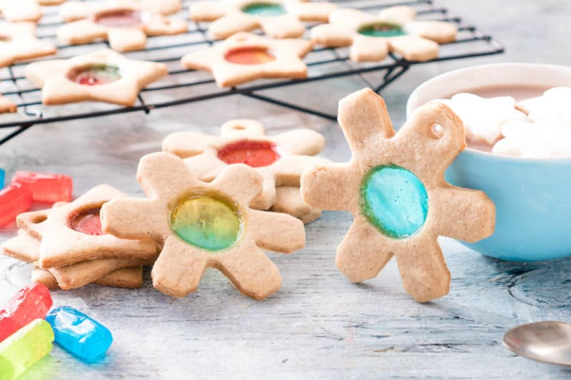 Snowflake shaped sugar cookies with center circle of stained glass and Jolly Ranchers next to them