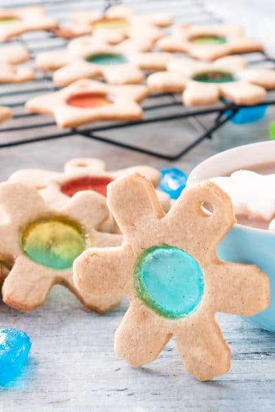 Snowflake shaped sugar cookie with blue circle of Jolly Rancher stained glass