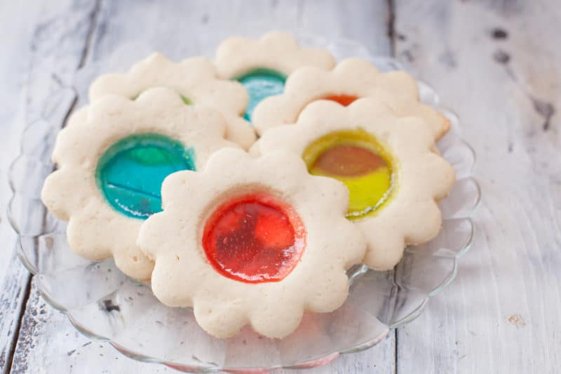 Flower shaped stained glass cookies with red, blue, and yellow see through centers