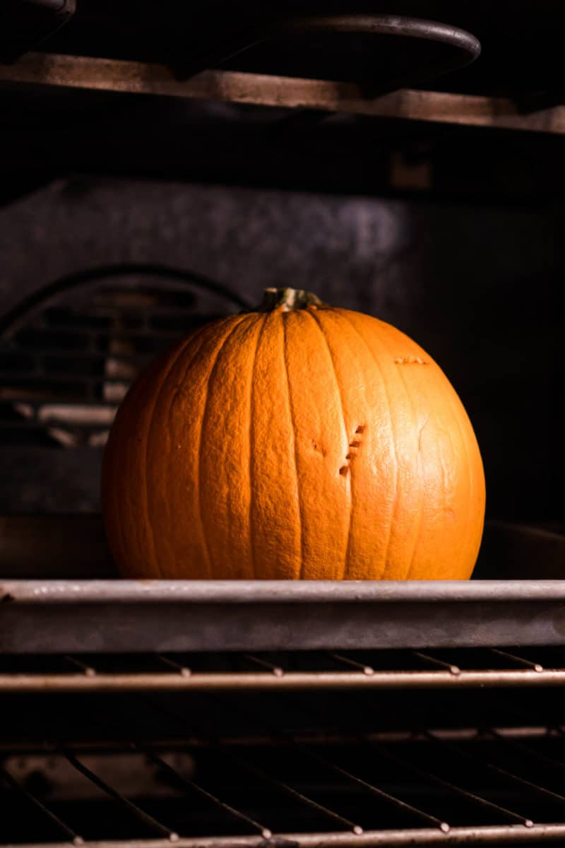 A whole roasted pumpkin sitting on a cookie sheet in a dark oven
