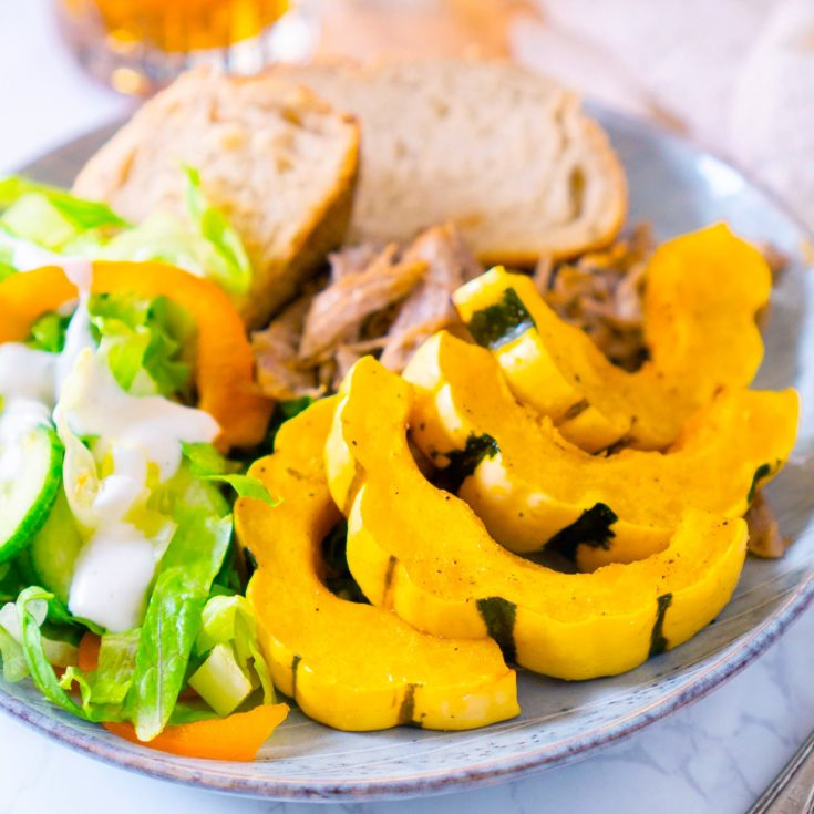 roasted delicata squash on blue plate with salad, bread slices, and pulled pork