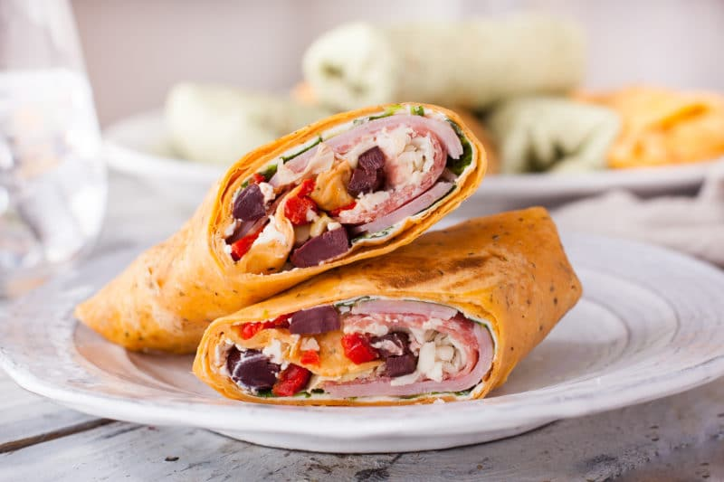 Italian wrap cut in half to show antipasto ingredients