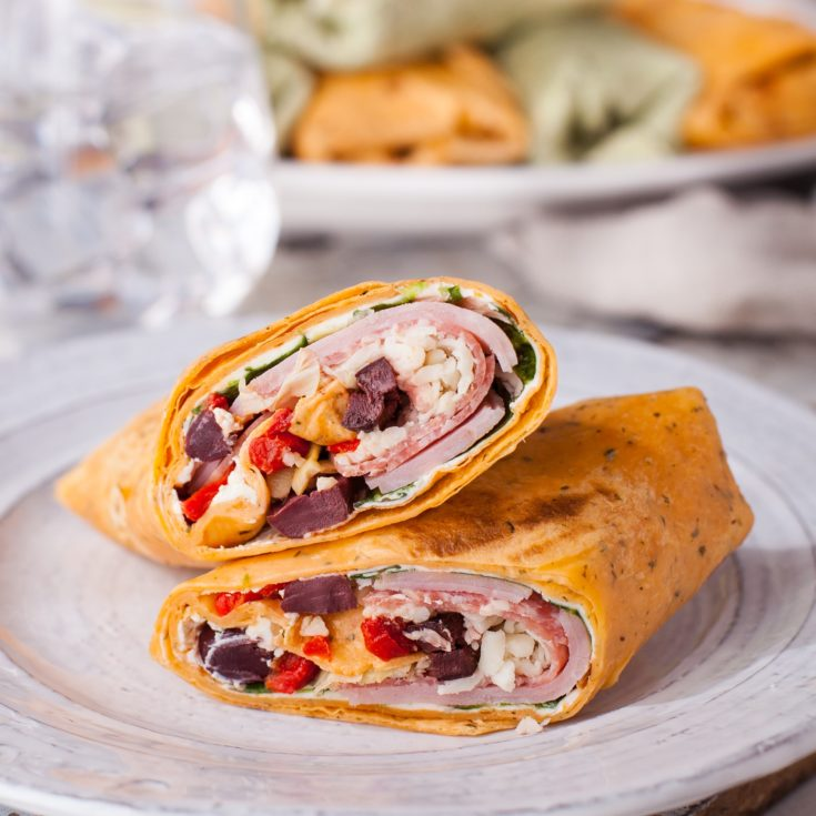 Two halves of an Italian wrap on a white plate with whole wraps in the background