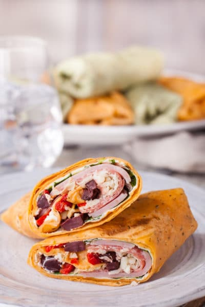 Two halves of Italian wrap stacked on each other on a white plate with whole wraps in the background