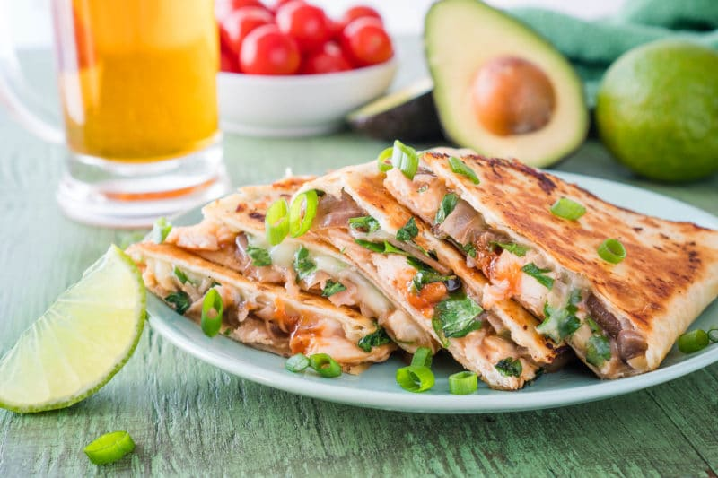 BBQ Chicken quesadilla triangles on a mint green plate with a lime wedge and cilantro