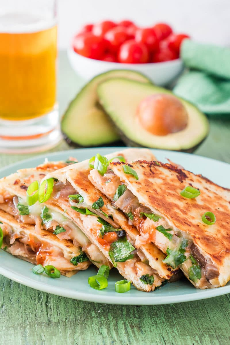 BBQ Chicken Quesadilla sliced into wedges with a glass of beer and avocado halves in the background